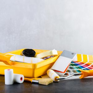 Color samples catalog, brush, paint tray and paint rollers, different painting tools on dark background. Concept of renovation, choosing and major repair